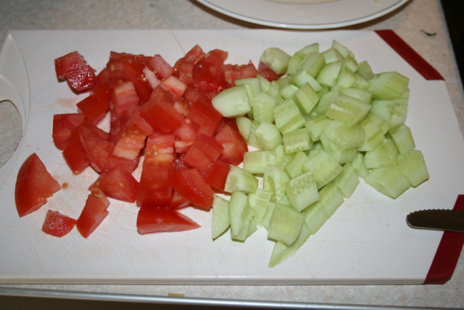 Pa virsu uzber sagrieztu tomātu un gurķi.