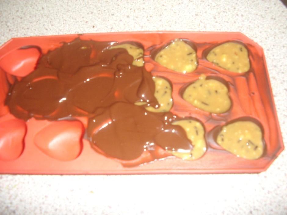 Kad šokolāde sacietējusi, konfektes piepilda un pa virsu pār...