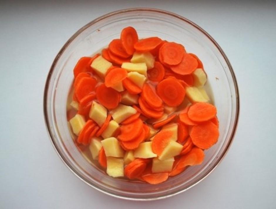 Notīra kartupeļus un burkānus, sagriež tos.