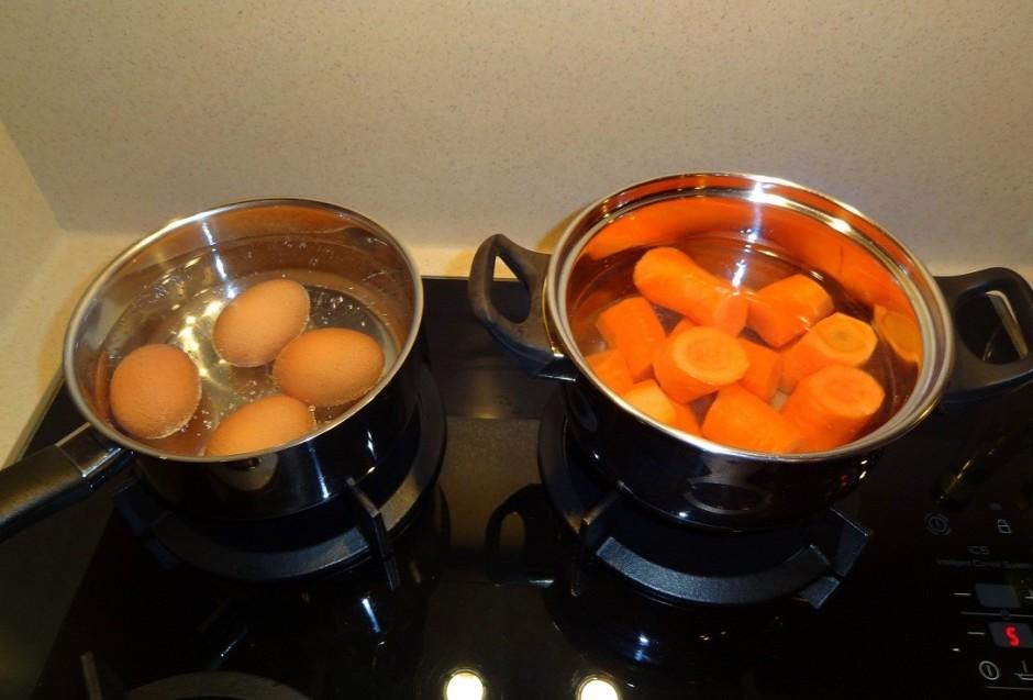 Uzvāra 4 olas, lai tās būtu cietas. Uzvāra notīrītus burkānu...