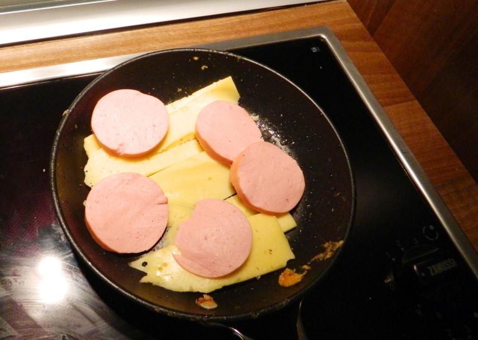 Kad eļļa uzkarsusi, uz pannas liek sagriezto sieru un desu.