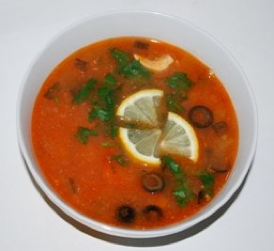 Zupu lej šķīvī, pievieno citrona šķēles, zaļumus, krējumu pē...