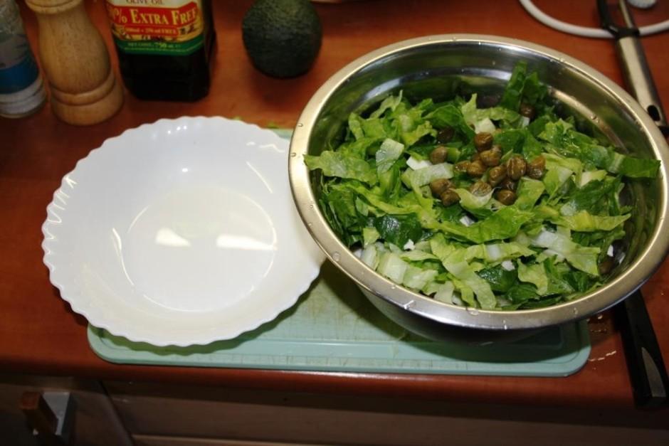 Sagriež salātus, garnelēm notecina šķidrumu un ieber traukā.