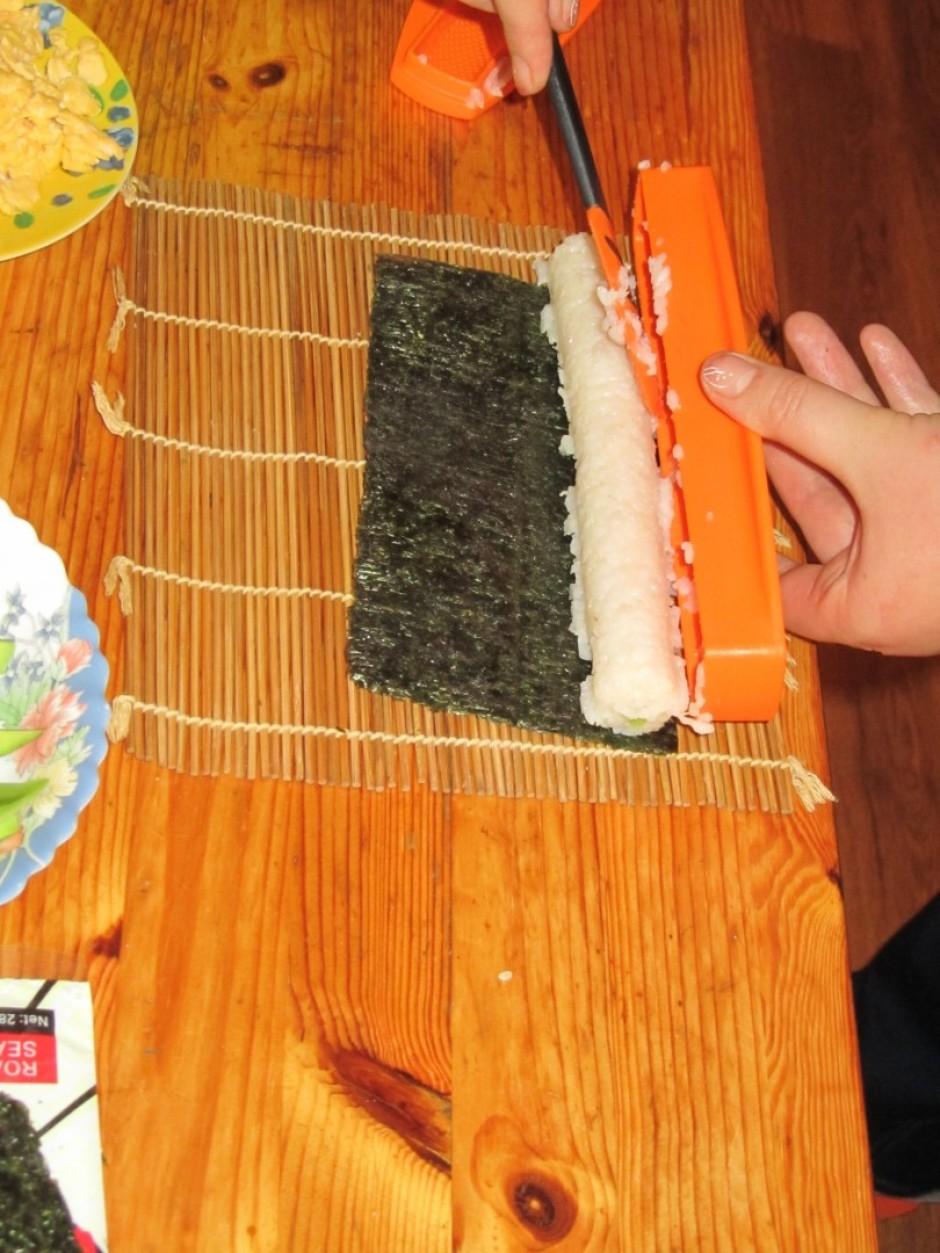 Tad uzklāj vēl nedaudz rīsus pa virsu un saspiež abas formas...
