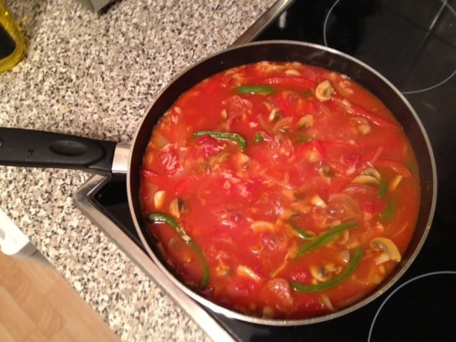 Iemaisa rīsus, sasmalcina tomātus un pievieno 500 ml karsta...