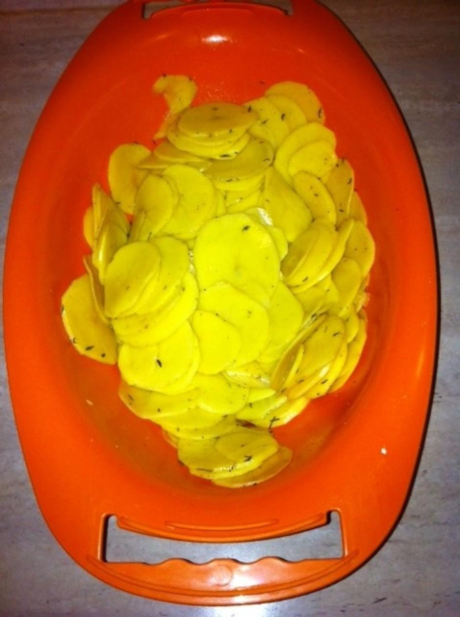 Nomizo un uz rīves sarīvē kartupeļus plānās 1.5 mm šķēlītēs,...
