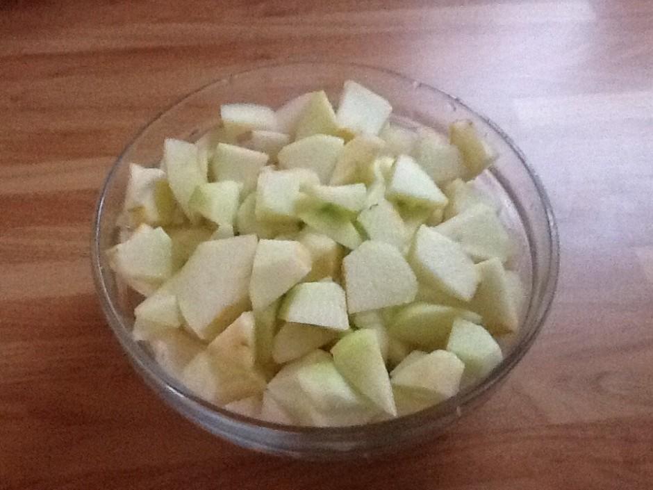 Kamēr cukurs kūst, sagriež ābolus un bumbierus kubiciņos, pi...