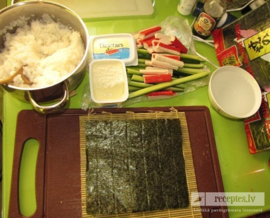 Ņem bambusa paklājiņu, liek suši nori lapu ar spīdīgo malu u...