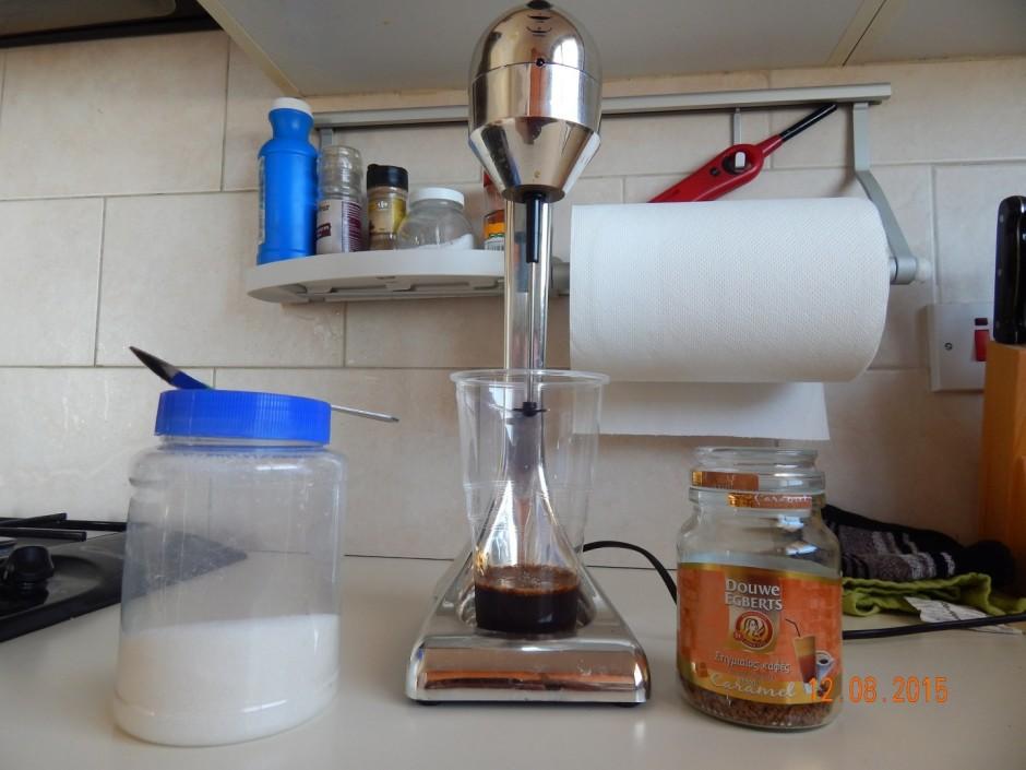 Glāzē ieber kafiju un cukuru, ielej mazliet auksta ūdens.