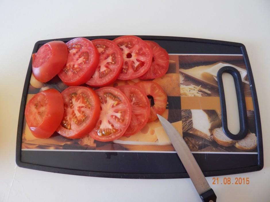 Nomazgā tomātus un sagriež šķēlītēs, sarīvē sieru.
