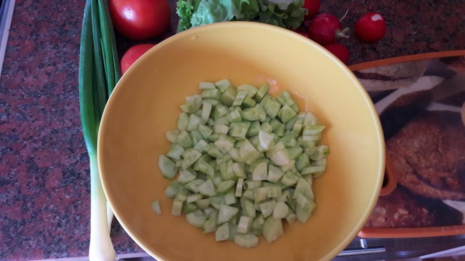 Nomizo un sagriež gurķus. Ieber bļodā, kurā jauks salātus.