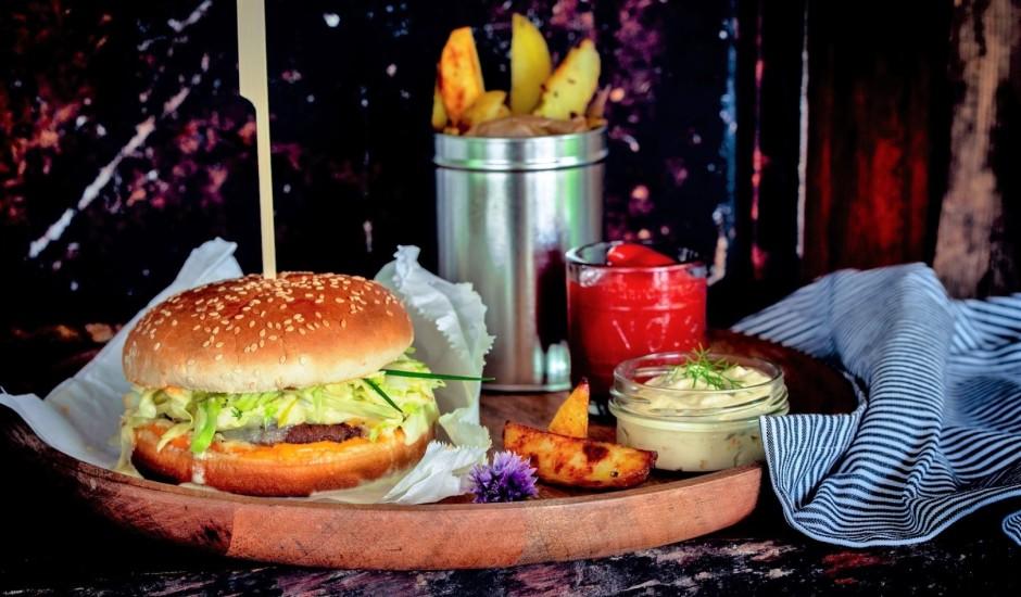 Burgers ar kāpostu salātiem un krāsnī ceptiem frī kartupeļiem ar ķimenēm
