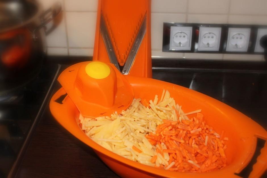 Salmiņos sarīvē kartupeļus un burkānus, liek zupas katlā vār...