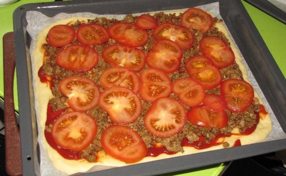 Sagriež tomātus šķēlītēs un liek uz gaļas.