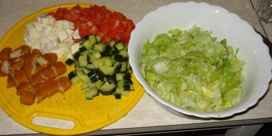 Rupji sagriež salātus, dārzeņus un sieru.Sagriež izceptos zi...