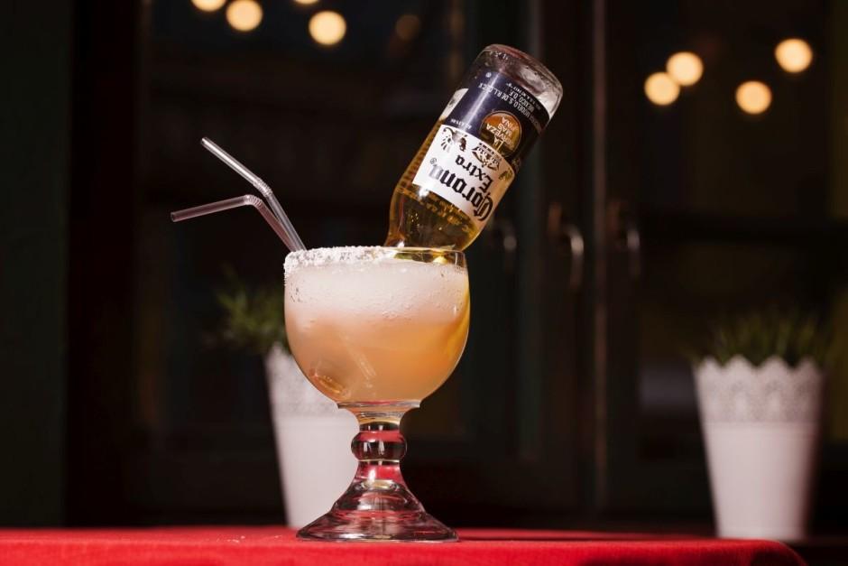 """Nobeigumā atver pudeli """"Corona"""" un ievieto to glāzē ar atvēr..."""