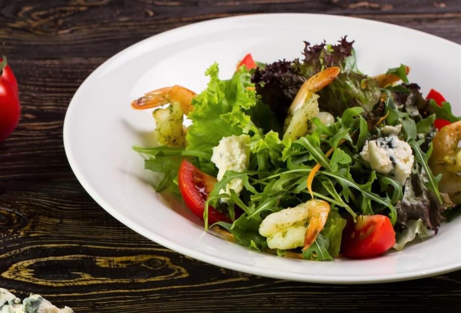 Uz šķīvja kārto salātu lapas, svaigu gurķu un tomātu gabaliņ...