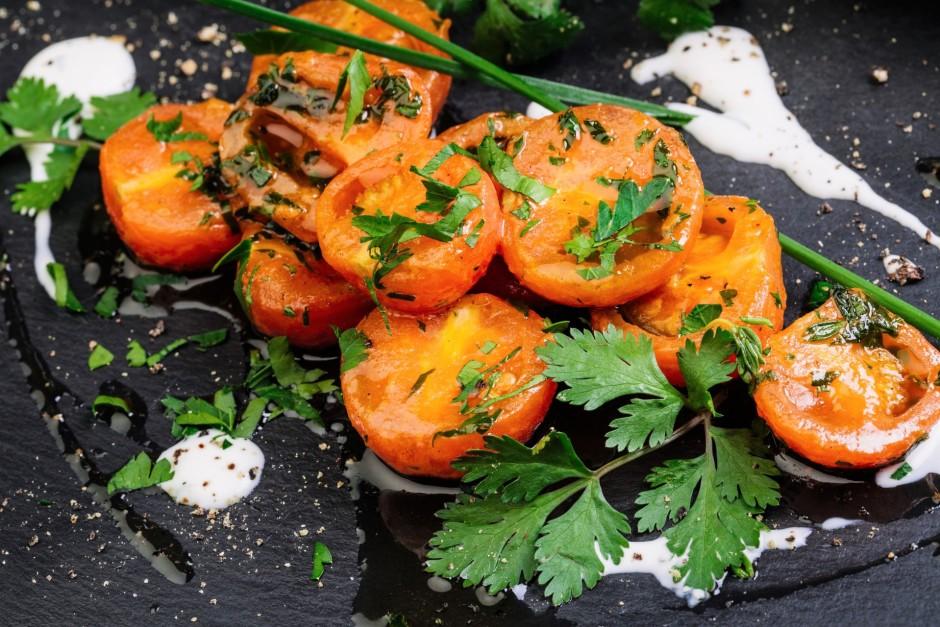 Pieliek uz pusēm pārgrieztus tomātus, sāli un piparus un mai...