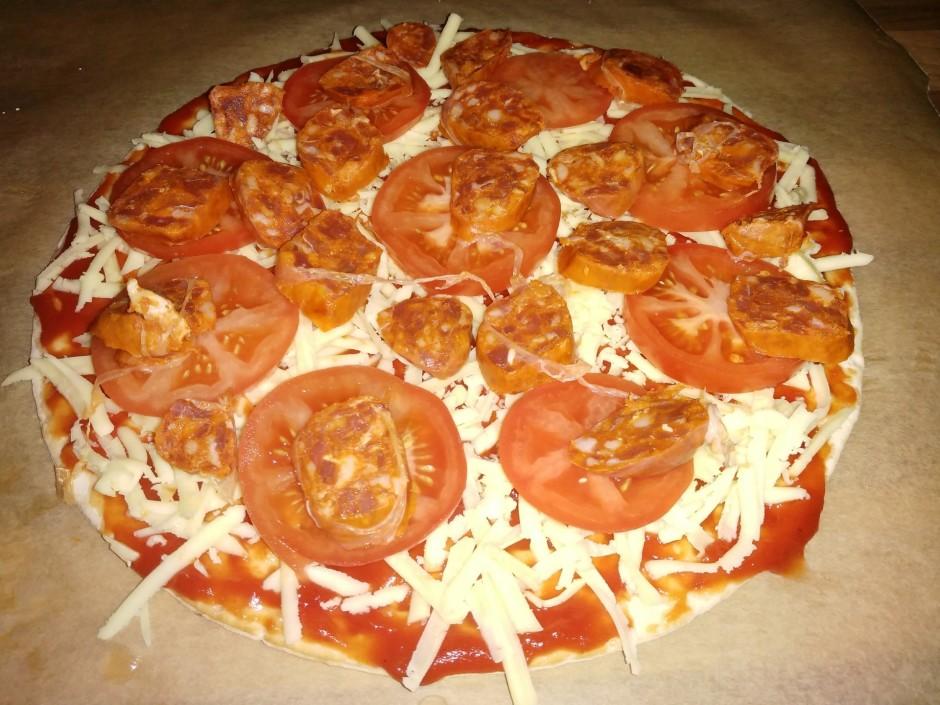 Sagriež desiņas un noklāj picas pamatni virs tomātiem.