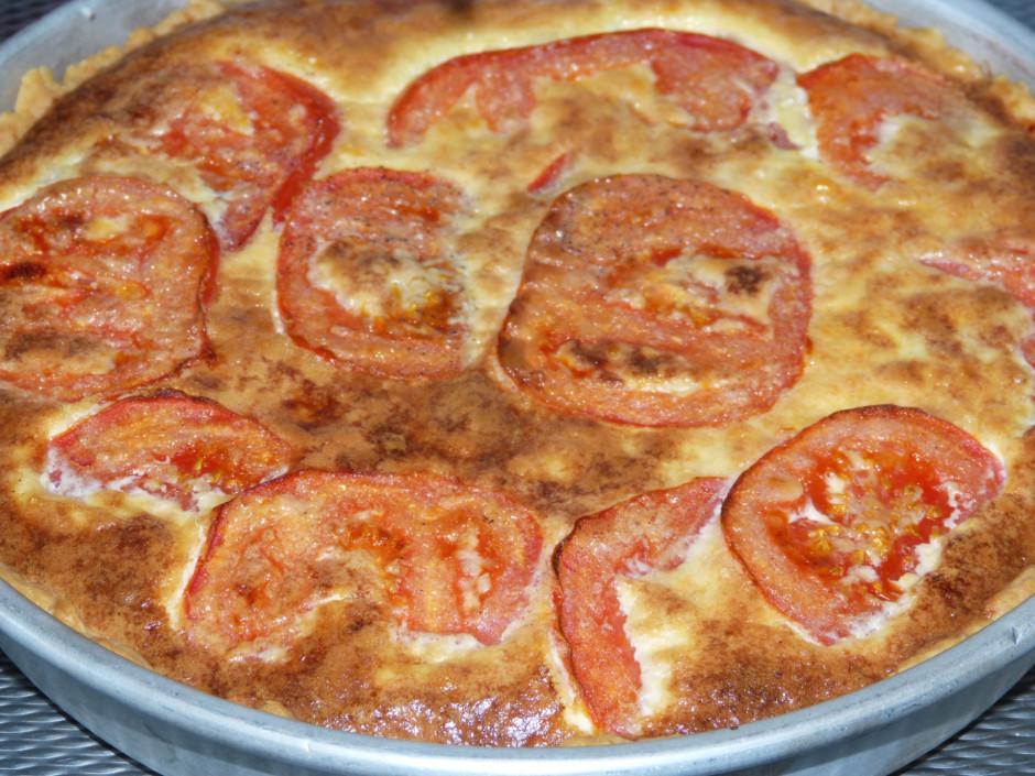 Uz mīklas izkārto sagrieztus tomātus, pārlej ar saputotu olu...