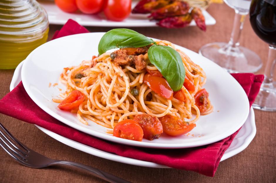 Pagatavoto tomātu, tunča un kaperu mērci iemaisa spageti. Da...