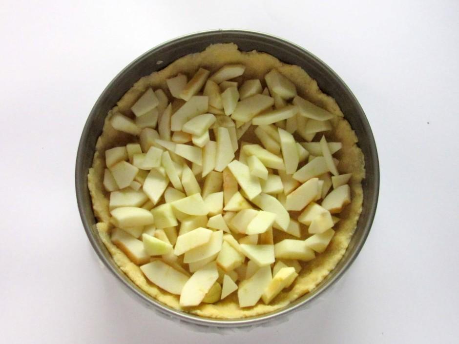 Notīra ābolus, sagriež šķēlītes un sakārto uz ieklātās mīkla...