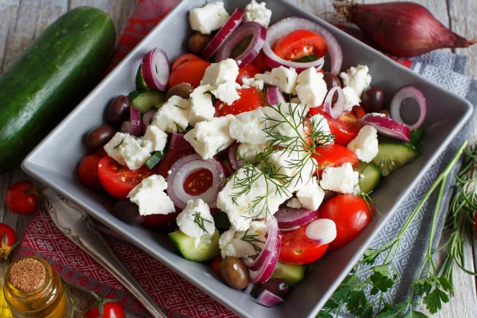 Virs dārzeņiem uzdrupina sieru un dekorē ar zaļumiem.  Lab...