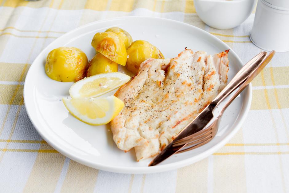 Pasniedz ar citrona daiviņām un vārītiem apceptiem kartupeļi...