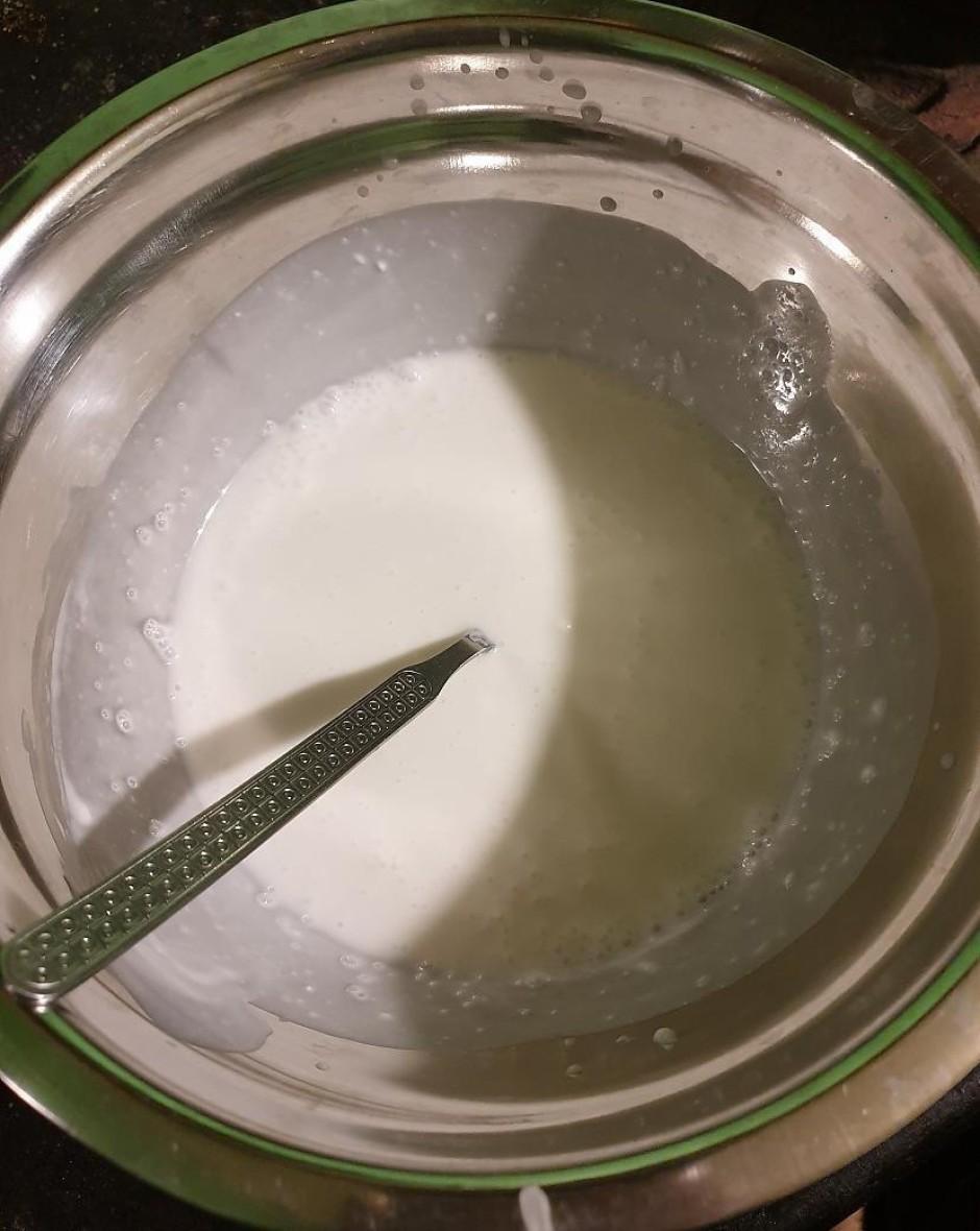 Metāla bļodā lej kokosriekstu piena bundžas saturu un liek s...