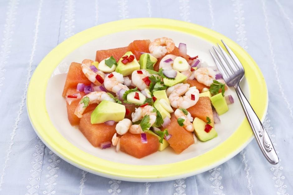 Salātus liek šķīvī, kārto virsū garneles, pārber ar sīpoliem...