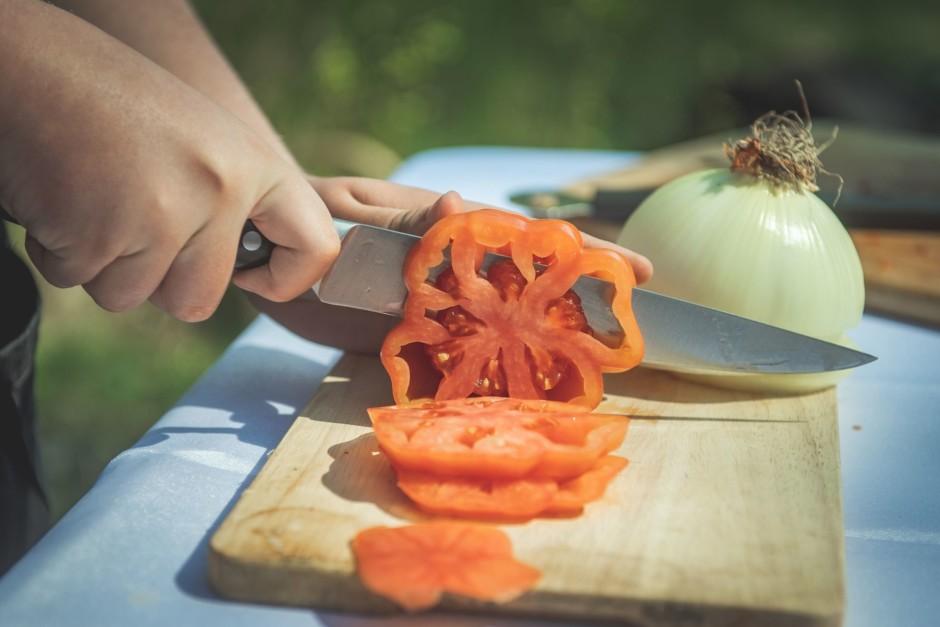 Biezās šķēlēs sagriež saldo sīpolu, tomātu.