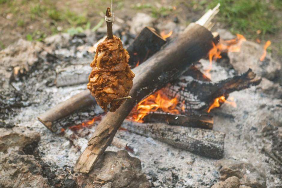 Apsien ar striķīti un iekarina blakus ugunskuram trejkājī, l...