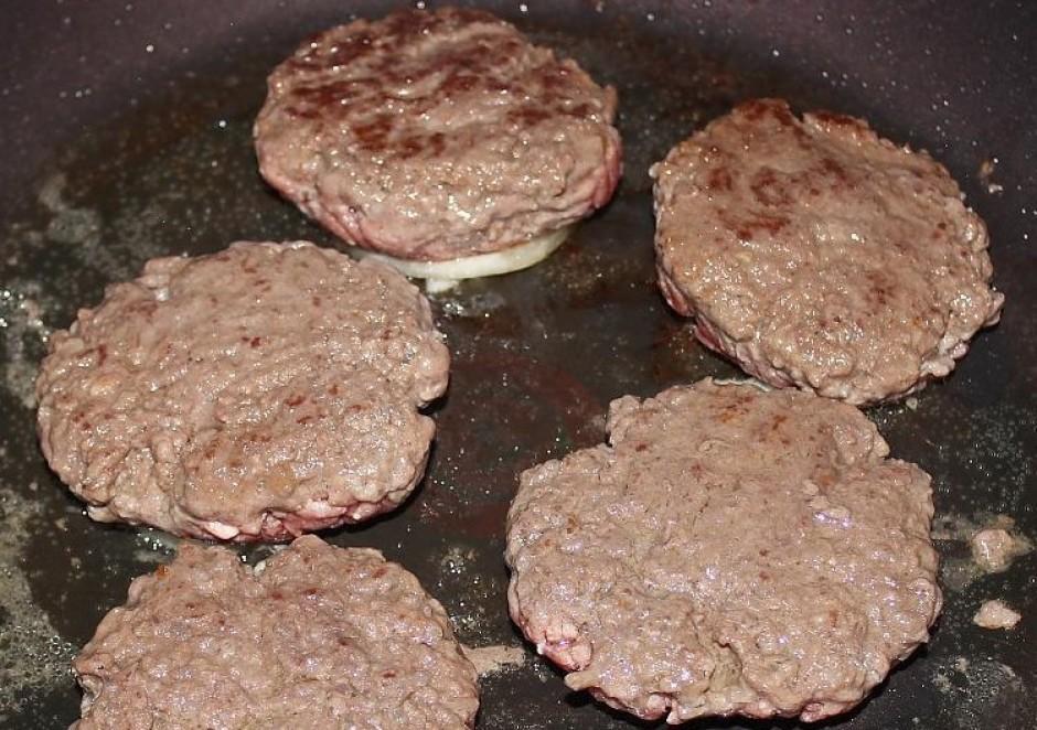 Met burgera kotletes riņķī un karamelizē apakšā sīpolus.