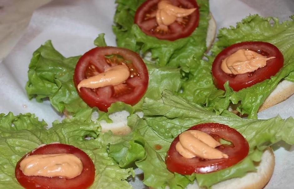 Uz maizītes vienas puses krāmē virsū salātlapas, tomātus, bu...