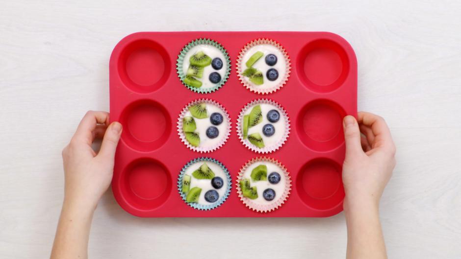 Virsū lej jogurtu un papildina ar kivi un mellenēm.