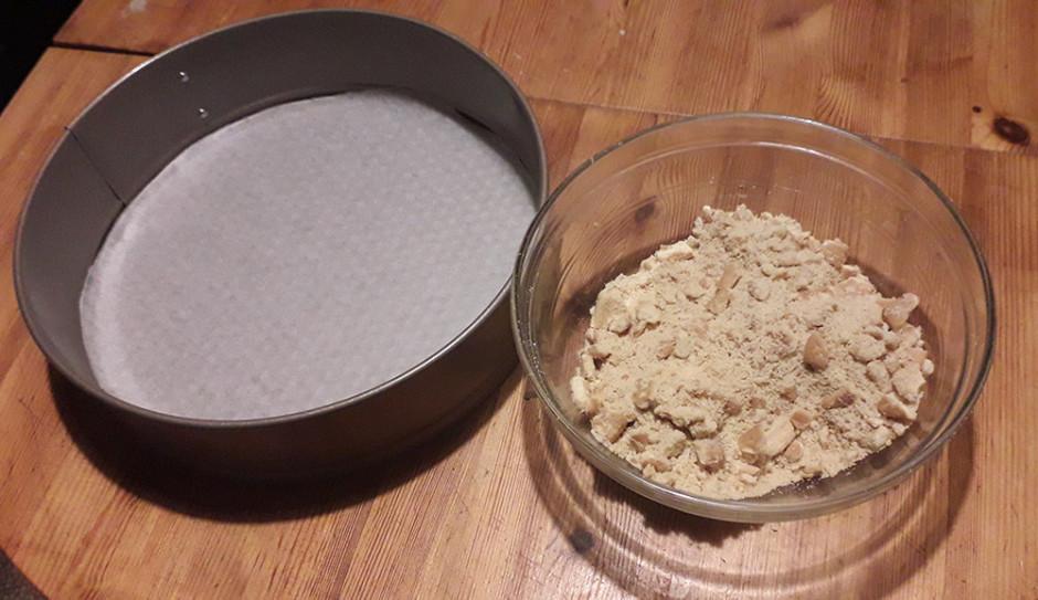 Tortes formā ieklāj, cepamo papīru. Sadrupina cepumus.