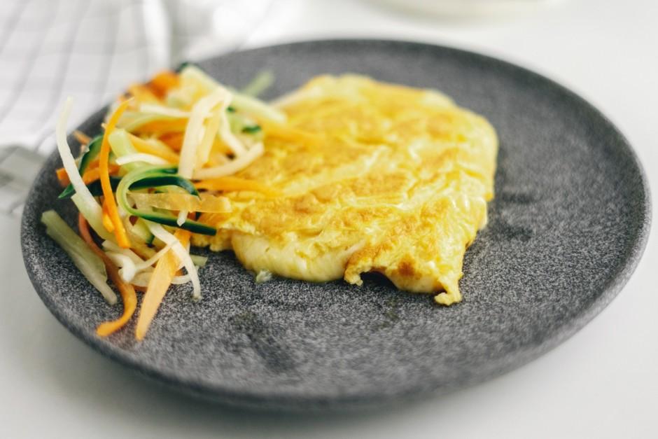 Uz šķīvja kārto silto omleti kopā ar svaigajiem salātiem....