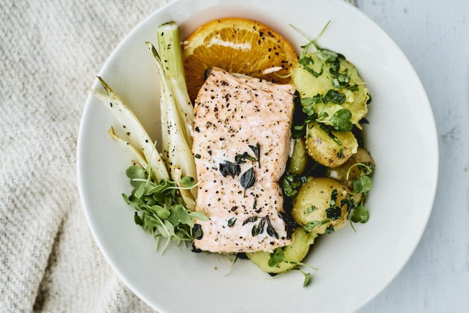 Pasniedz, kārtojot šķīvī zivi, fenheli un kartupeļu salātus....